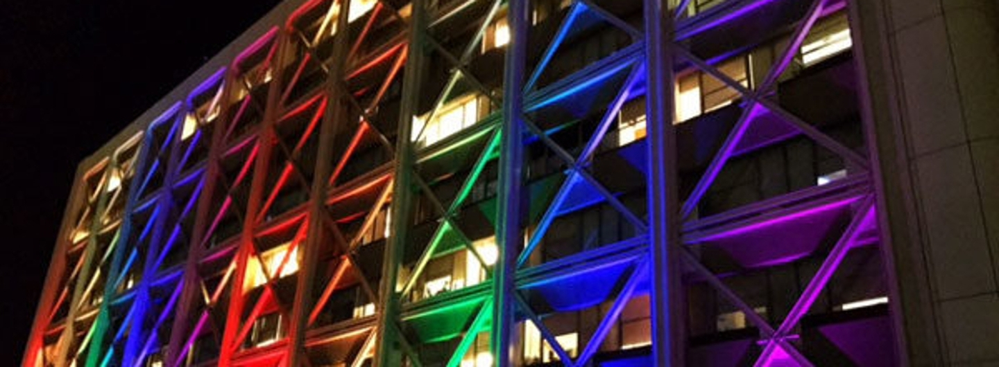 the UC San Diego hospital at night with lights streaming across its facade in the pride colors